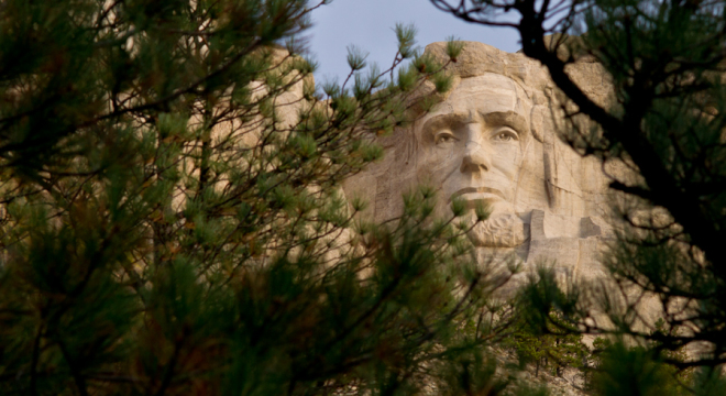 Abe Lincoln peeks out from the trees at Mount Rushmore